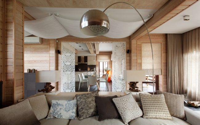 Белый тканевый потолок хорошо смотрится с деревянной отделкой гостиной