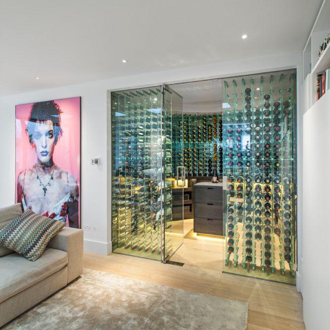 Зона гостиной выглядит более эффектно в соседстве с остеклённым хранилищем винной коллекции