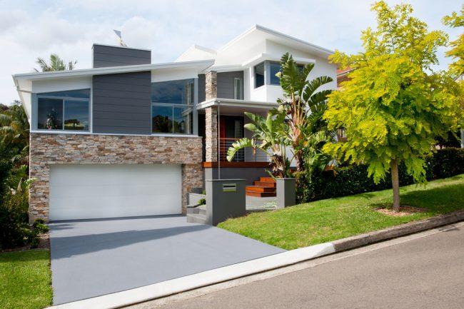 Прекрасное сочетание белоснежных ворот и фасада гаража, отделанного декоративным камнем