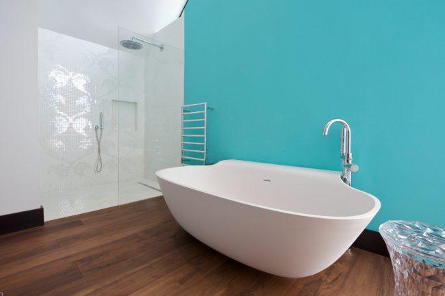 Украсить стену в ванной комнате можно сочетанием керамической и стеклянной мозаики одного тона, создав незамысловатый рисунок