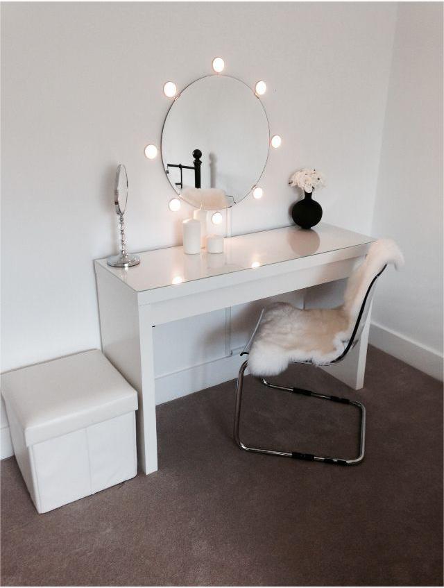 Небольшое круглое зеркало с отдельно установленной подсветкой и небольшим туалетным столиком в стиле минимализм