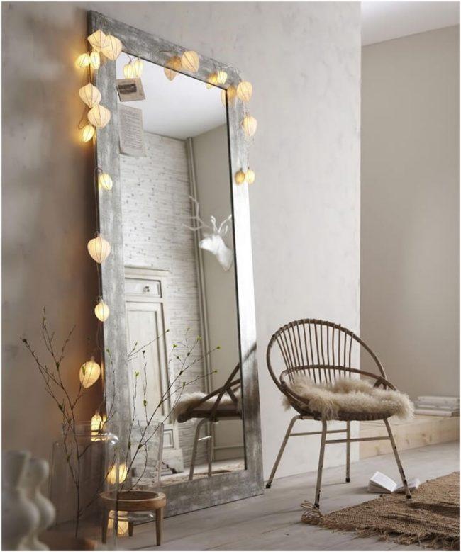 Один из легких вариантов получить зеркало с лампами - это декор крупными гирляндами