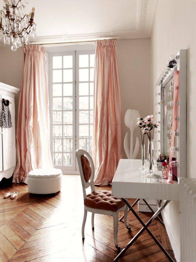 Красивое зеркало в белой оправе с туалетным столиком и подсветкой в детской комнате