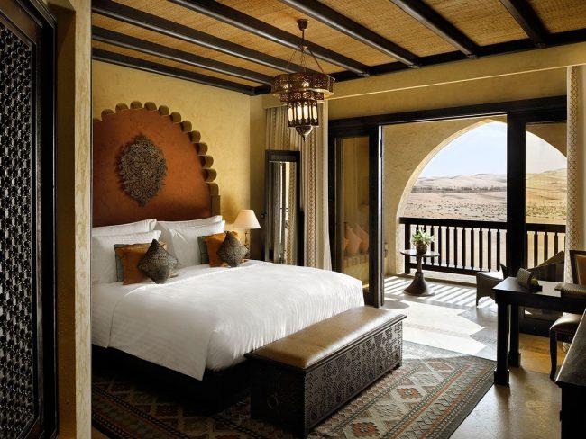 Деревянные балки на потолке, большие окна, ковер с восточными элементами в интерьере спальни