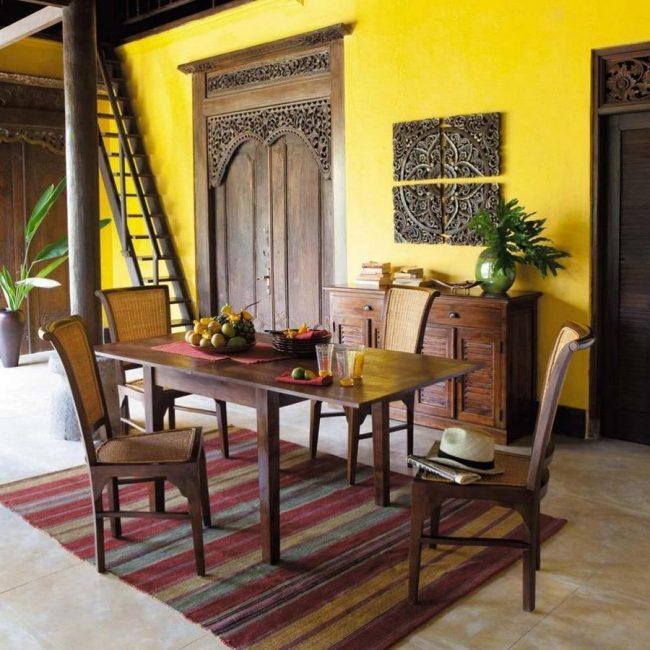 Желтая кухня в колониальном стиле с резными элементами и ярким ковром