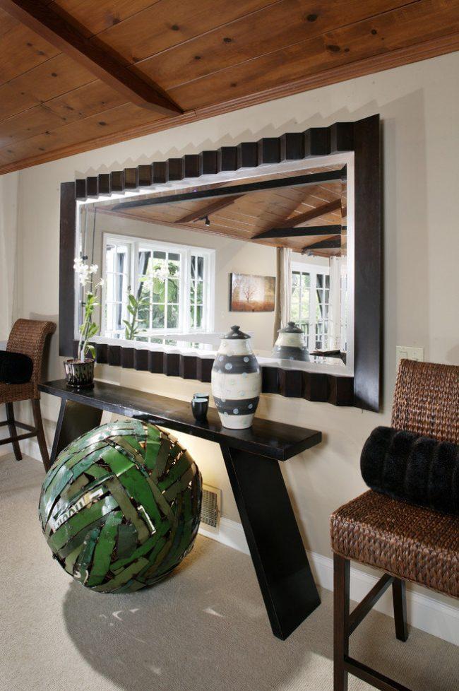 Простые формы небольшого столика в виде лавки подчеркнут оригинальность массивного зеркала