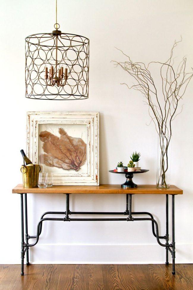 Узкий столик в гостиной на четырех кованых ножках