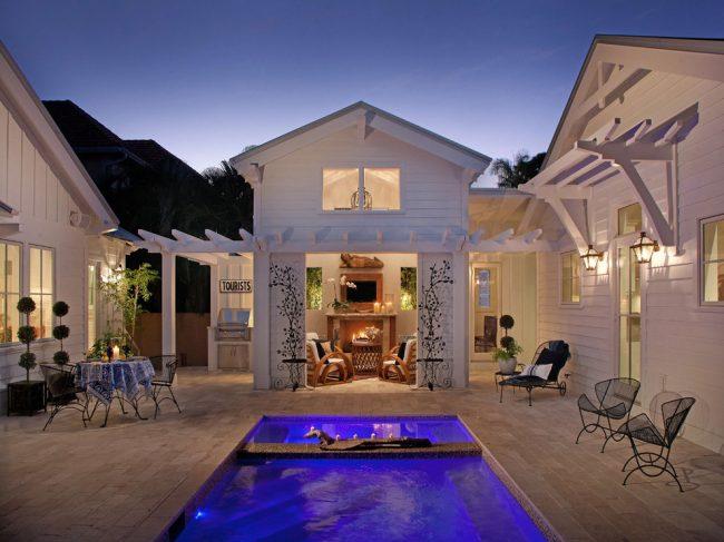 Просторный красивый дворик с бассейном внутри коттеджа из двух домов
