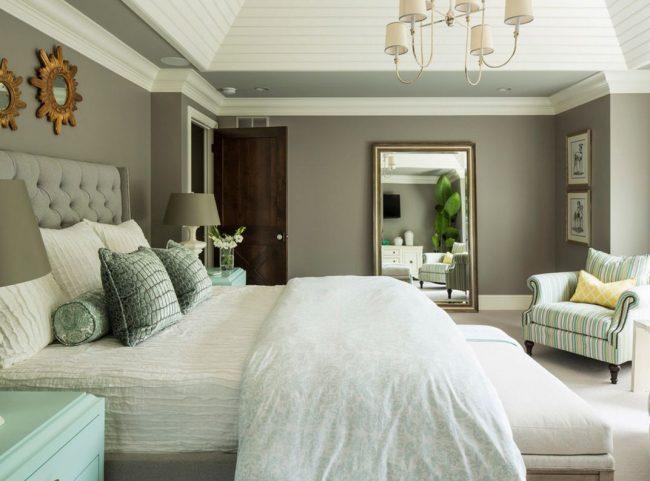 Светлая полосатая обшивка кресла гармонично сочетается с подушками и тумбами спальни