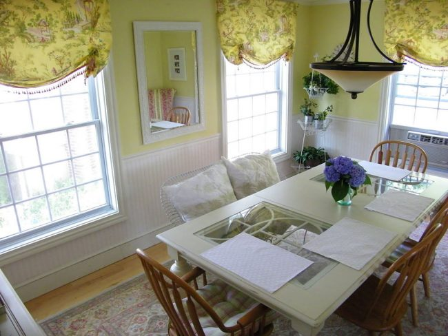 Нежная и уютная столовая благодаря светлым оливковым оттенкам стен и штор