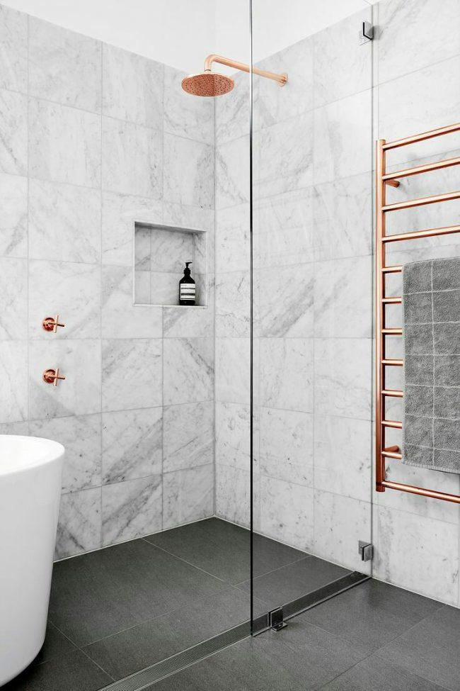 Светлая серая ванная комната с медными элементами сантехники