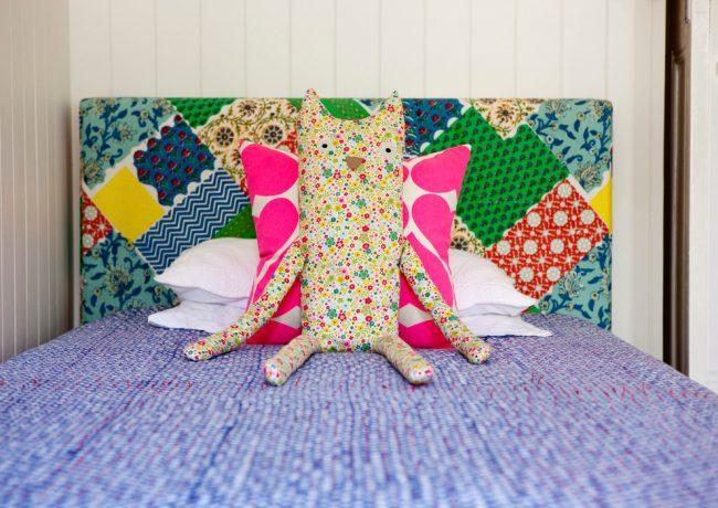 Изголовье детской кровати декорировано ситцевыми лоскутами пэчворк