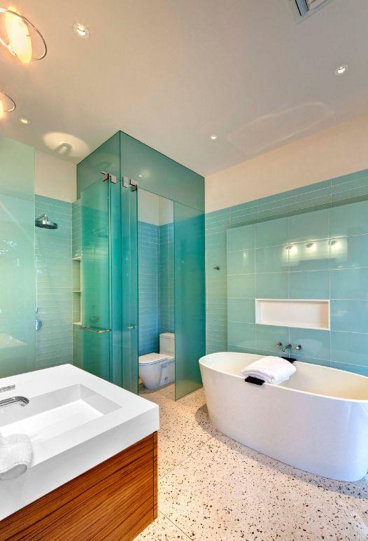 Плитка стеклянная для кухни и ванной: оформление зоны ванной с помощью крупной плитки голубого цвета