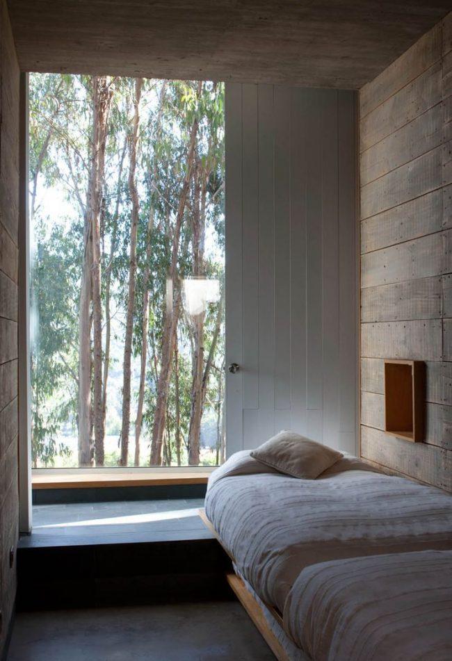 Уютная спальня в частном доме с низким подоконником-столешницей, который отлично заменяет прикроватный столик