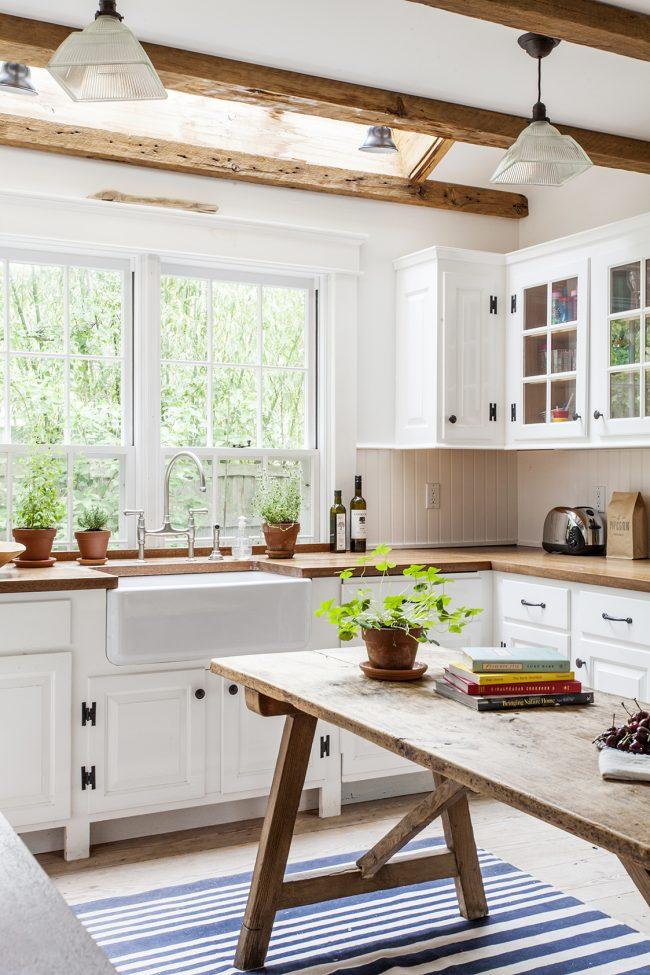 Светлая кухня с яркими акцентами на деревянных элементах мебели. Обратите внимание как подоконник-столешница плавно переходит в кухонный гарнитур