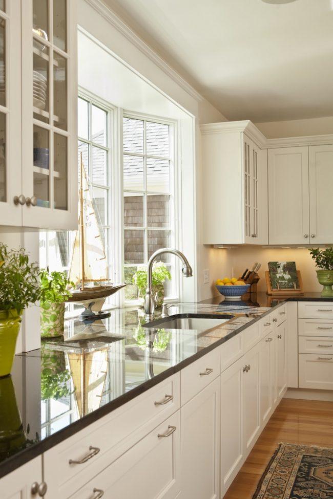 Кухня частного дома с нестандартной, выступающей наружу оконной рамой, которая позволяет увеличить площадь рабочей поверхности подоконника-столешницы