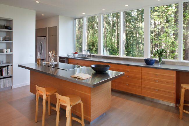 Просторная кухня с большим панорамным окном практически на всю стену. Подоконник-столешица очень органично выглядит в данном варианте оформления пространства