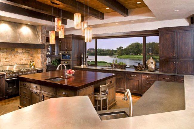 Роскошная кухня с деревянным кухонным гарнитуром и панорамным окном на всю стену, оформленным подоконником-столешницей