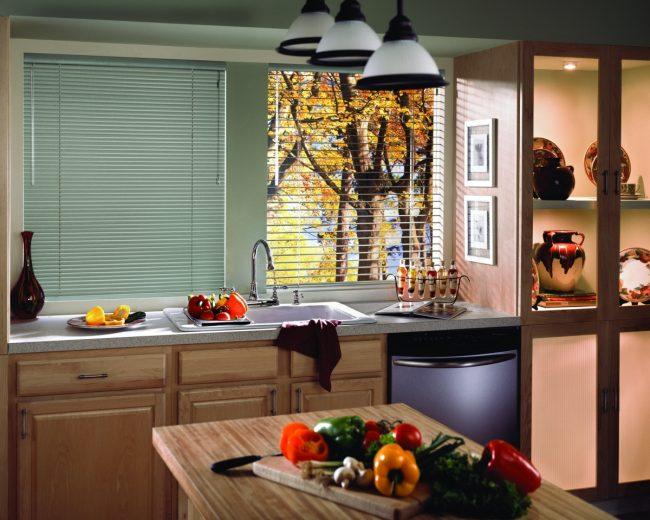 Небольшая кухня в пастельных тонах с деревянным кухонным гарнитуром и очень практичным подоконником-столешницей