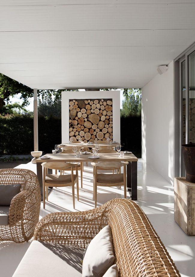 Поленница с уложенными в нее дровами может стать центром внимания летней площадки в дворе частного дома