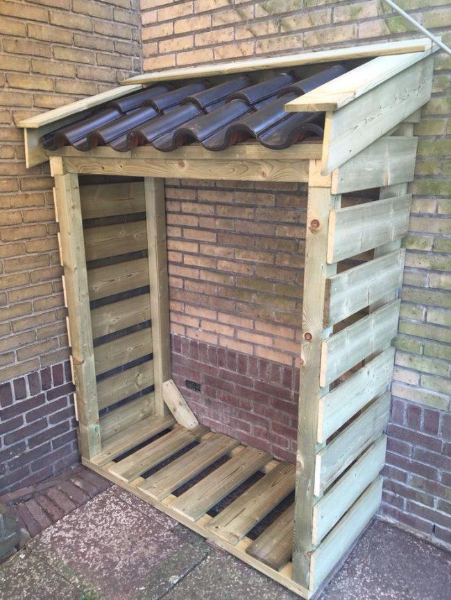 Установить поленницу для дров можно прямо у фасада дома. Такая конструкция очень проста в исполнении и достаточно удобна в использовании