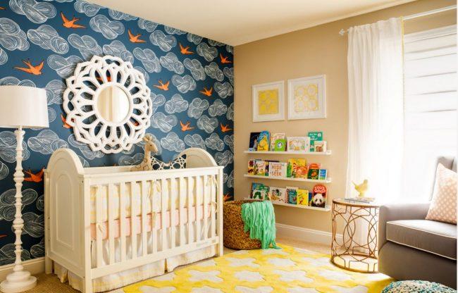 Интересный пейзаж возле детской кроватки: синие обои с тучками, птицами и зеркало в виде солнца