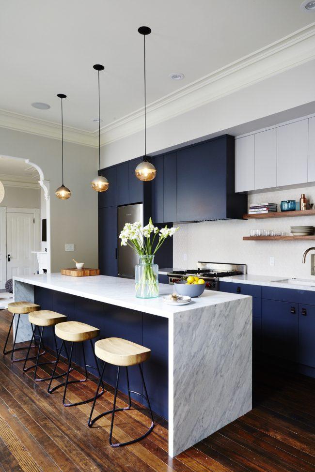 Кухня в синих тонах с теплыми акцентами на деревянной мебели и паркете из натурального дерева