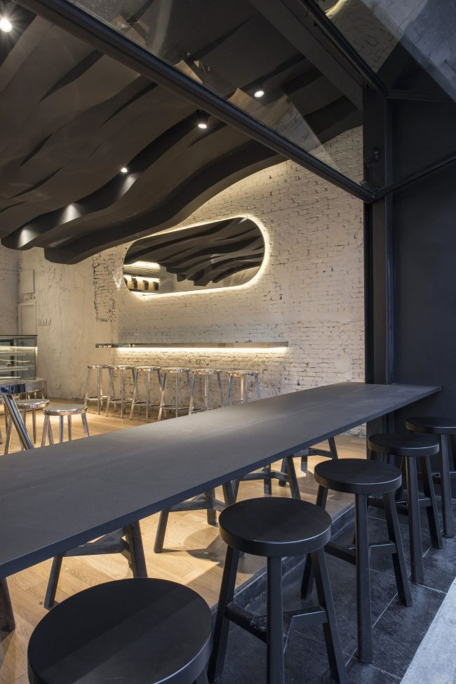 Фактурный черный потолок с точечными светильниками в интерьере кухни