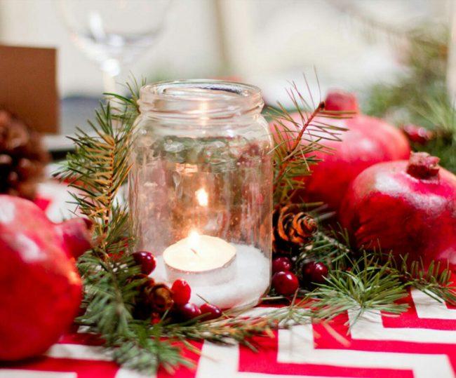 Контрастное оформление стола из еловых веток с шишками, свечей и граната