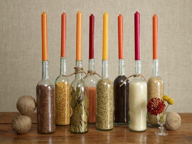 Оригинальные подсвечники из бутылок, наполненных разными крупами, порадуют Огненного Петуха