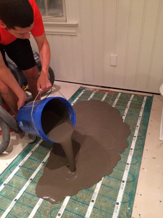 Теплый водяной пол с использованием бетонной подушки. На фото вы можете увидеть процесс заливки бетона