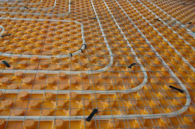 Вместо деревянных лаг для закрепления труб вы можете использовать уже готовую основу для теплого водяного пола, которую можно найти во многих строительных магазинах