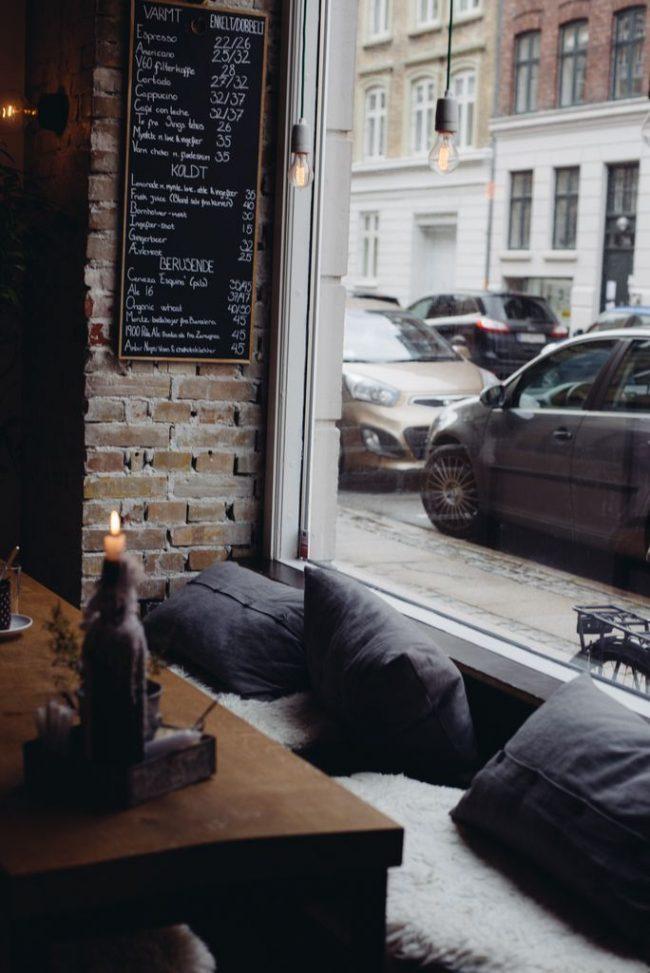 Мягкие подушки у окна и кирпичная стенка - это хороший вариант для оформления небольшой кофейни в стиле лофт