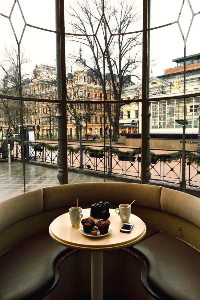 Круглый мягкий диванчик с небольшим столиком по центру и красивым видом из окна