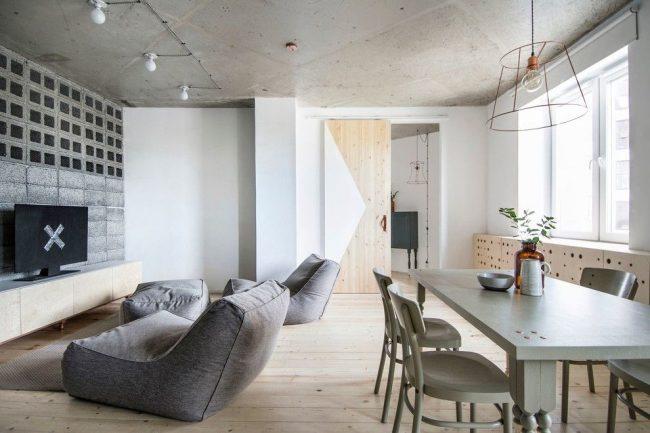Светлая гостиная с бетонным потолком и деревянной дверью