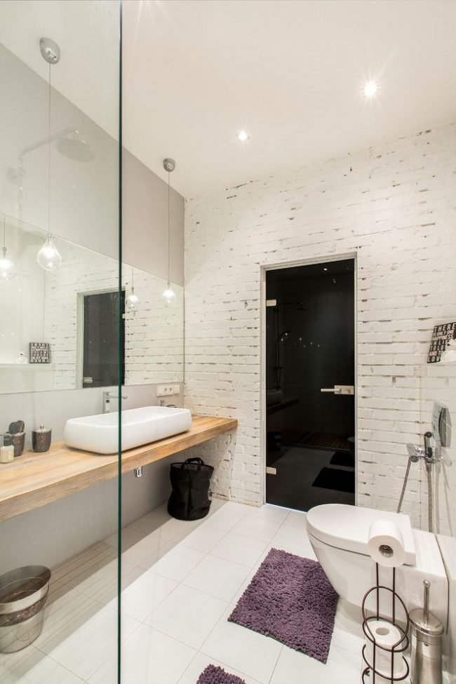 Белая кирпичная стена и черная дверь в стильной и современной ванной комнате