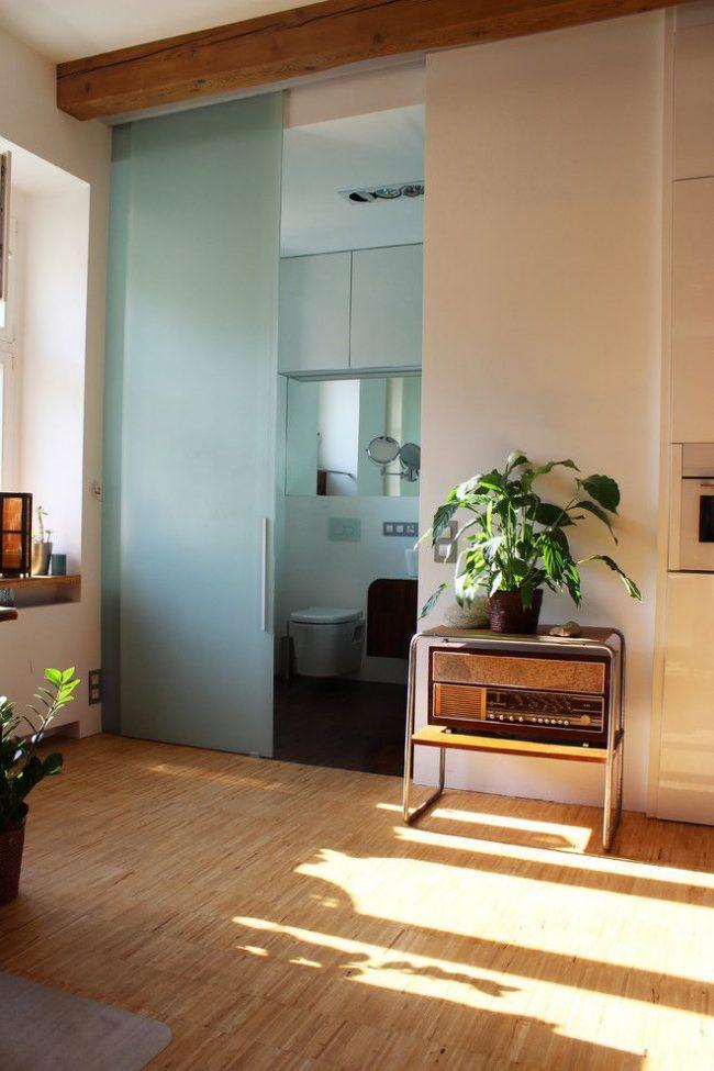 Сдвижная дверь из матового стекла хорошо смотрится в индустриальном стиле
