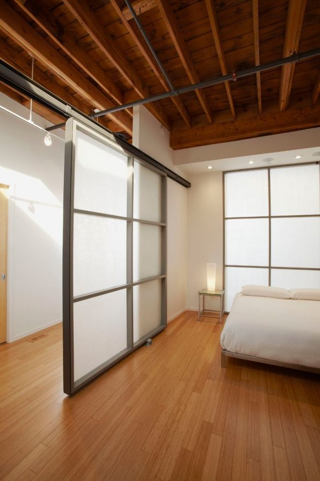 Светлая спальня со сдвижной дверью из матового белого стекла и металла