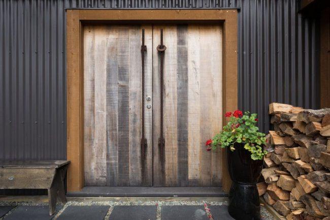Массивные деревянные входные двери с ручками из металлических прутьев