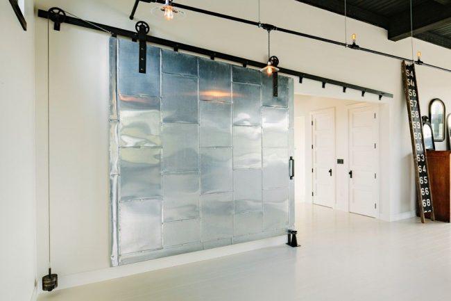 Широкая дверь из металлических листов выглядит достаточно ярко и необычно
