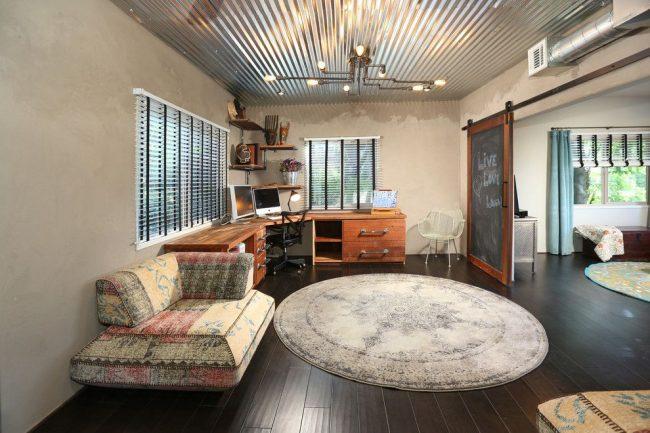 Металлический потолок и необычная дверь в интерьере стиля лофт