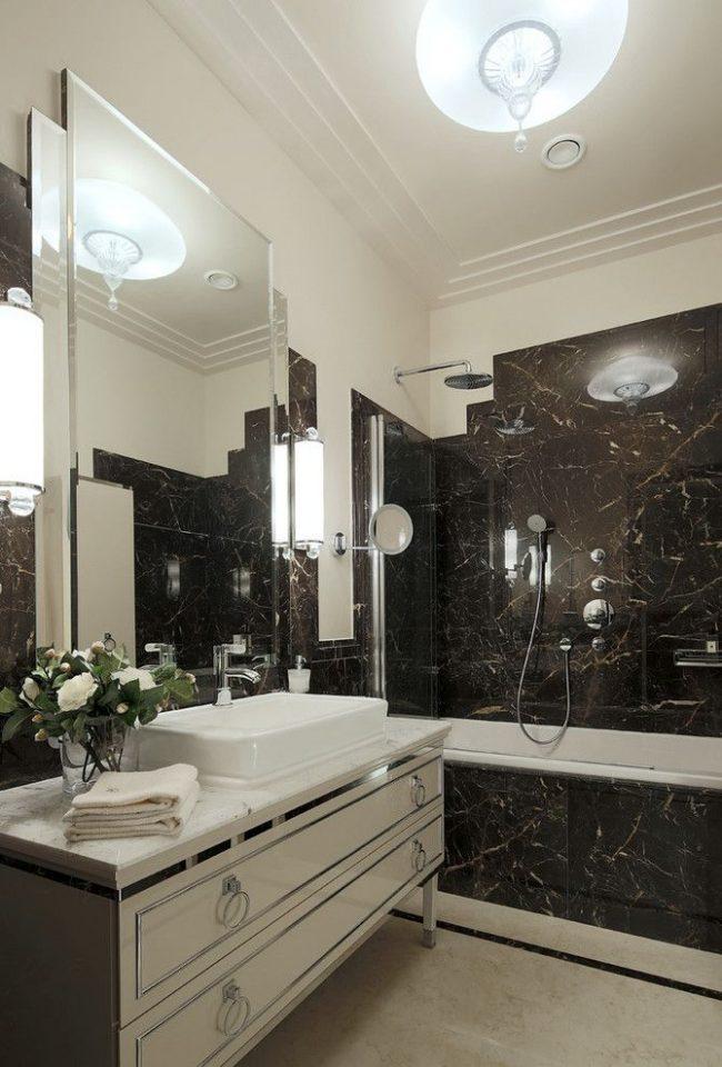 Белый потолок и большое зеркало в маленькой ванной комнате блокируют эффект темных стен и визуально увеличивают площадь