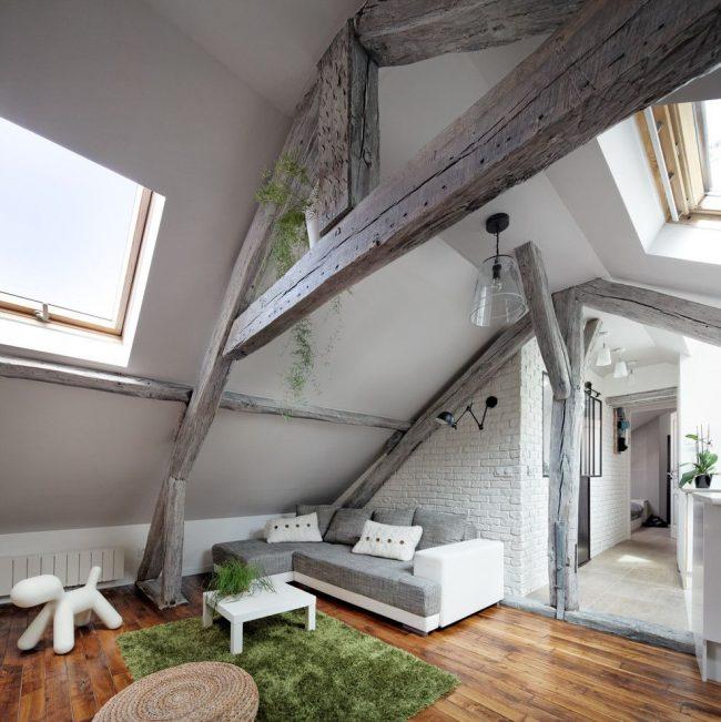 Уютный интерьер под крышей в скандинавском стиле с обилием белого цвета и деревянными балками