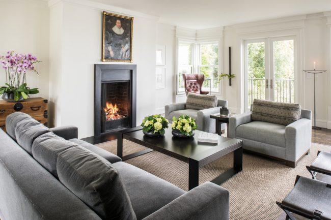 Прямой диван темно-серого цвета прекрасно впишется в интерьер классической гостиной