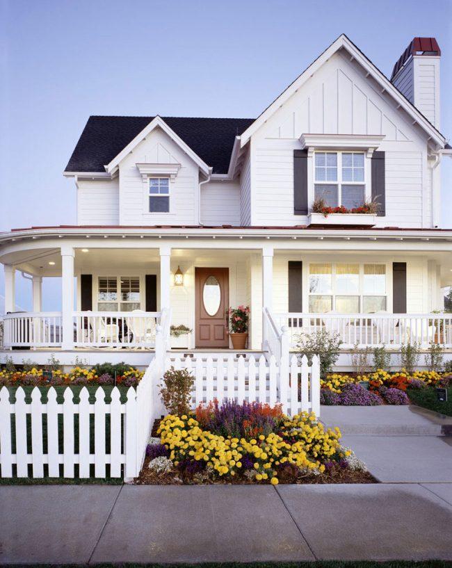 Белоснежный дом с красивым деревянным забором в классическом стиле
