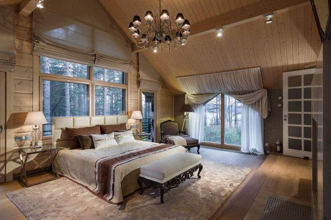 Классические портьеры и римские шторы в просторной спальне деревянного дома