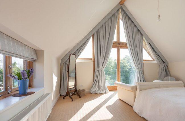 Шторы на мансардные окна: огромное треугольное окно на всю стену с классическими портьерами придают интерьеру особой роскоши