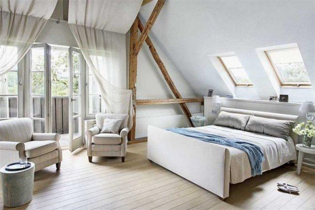 Красивые полотняные шторы, свисающие с потолка в мансардной спальне