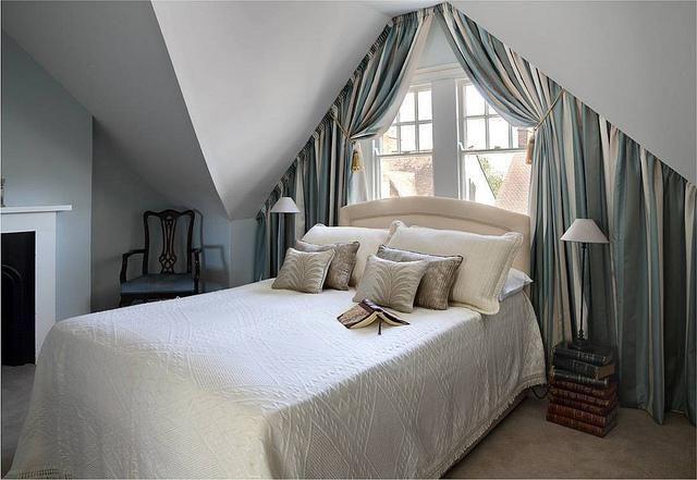 Классические плотные портьеры в небольшой мансардной спальне