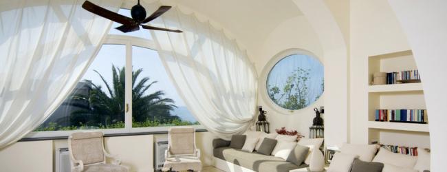 Арочное окно с соответствующим карнизом и белыми шторами